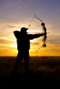 Bowhunter at sunset an full draw silhouetted against a Stock Image