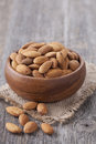 Bowl with almonds nuts on wooden table Royalty Free Stock Photo