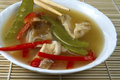 Bowl of asian chicken soup on bamboo with red pepper and snow peas in white mat with chopsticks Royalty Free Stock Photography