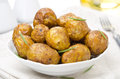 Bowl of baked new potatoes with spices and rosemary close up Stock Photography