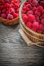 Bowl and bucket with red raspberries on wooden board Royalty Free Stock Photo