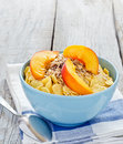 Bowl of cereal with muesli and fresh peach Royalty Free Stock Photos