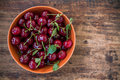 Bowl of cherries with leaves on the old wooden background rustic Stock Photos