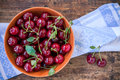 Bowl of cherries with leaves on the old wooden background rustic Royalty Free Stock Photos