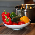 Bowl of colourful fresh vegetables including red yellow and green bell pepper and ripe red tomatoes standing on a kitchen counter Royalty Free Stock Image