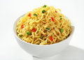 Bowl with cooked noodles vermicelli flavored green peas and chopped bell pepper in a white on white background Stock Images