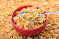Bowl with corn flakes on corn flakes background Royalty Free Stock Photo
