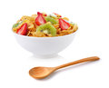 Bowl of corn flakes with fruit and wooden spoon Royalty Free Stock Photo