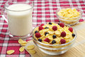 Bowl of cornflakes with berries and cup of milk Royalty Free Stock Photo