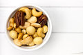 Bowl filled with nuts white on a wooden surface Royalty Free Stock Photo