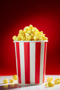 Bowl filled with popcorns for movie night red full of popcorn on red background film tv television watching concept of Royalty Free Stock Photography