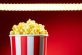 Bowl filled with popcorns for movie night with textspace red full of popcorn on red background film tv television watching concept Royalty Free Stock Photo