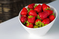 Bowl filled with succulent juicy fresh ripe red strawberries white Stock Photos
