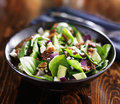 Bowl of fresh avocado spinach salad on wooden table top Royalty Free Stock Photos