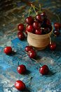 Bowl with fresh cherries on a wooden blue background. Ripe sweet cherries. Healthy food concept. Cherries in ceramic bowl.