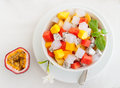 Bowl of fresh exotic fruit salad on white summer background Healthy breakfast Royalty Free Stock Photo