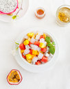 Bowl of fresh exotic fruit salad on white summer background Healthy breakfast Top view Royalty Free Stock Photo