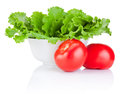 Bowl with fresh lettuce and two red tomatoes on white background Royalty Free Stock Photography