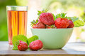 Bowl of fresh ripe strawberries and a glass of juice on a wooden table in the garden outdoors Royalty Free Stock Photo