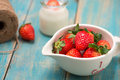 Bowl with fresh strawberry on blue wooden table. Royalty Free Stock Photo