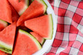 A bowl full of watermelon slices overhead shot wedges on checkered table cloth horizontal format half the is shown offset to Royalty Free Stock Photos