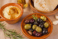 Bowl green black olives small pot hummus pita bread bottle olive oil leaf rosemary complete image Royalty Free Stock Photo