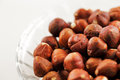 A bowl of hazelnuts on a white background shot against hazelnut is the nut the hazel and is also known as cobnut or filbert nut Stock Photos