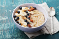 Bowl of homemade oatmeal porridge with banana, blueberries, almonds, coconut and caramel sauce on teal rustic table Royalty Free Stock Photo