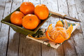 Bowl with honey tangerines and peeled tangerine on antique wood table Royalty Free Stock Photography