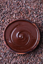 Bowl of melted chocolate on a crushed raw cocoa beans, nibs background. Copy space Top view Royalty Free Stock Photo