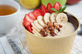 Bowl of oatmeal with a banana, strawberries, almonds, hazelnuts and butter on a rustic table. Hot and a healthy dish for Breakfast Royalty Free Stock Photo