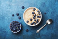 Bowl of oatmeal porridge with banana and blueberry on vintage table top view in flat lay style. Hot breakfast and homemade food. Royalty Free Stock Photo
