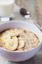 Bowl of oatmeal porridge with banana and caramel sauce on rustic table, hot and healthy breakfast Royalty Free Stock Photo