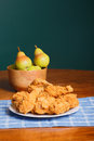 Bowl of pears behind plate of chicken a crispy fried on a white and a blue plaid placemat with a wood fresh Royalty Free Stock Images