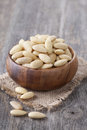 Bowl with peeled almonds nuts on wooden table Stock Images