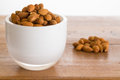 Bowl of raw almond nuts on wooden table Stock Images