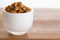 Bowl of raw almond nuts on wooden table Royalty Free Stock Photos