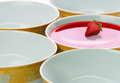 Bowl of red liquid five plates in a row with Royalty Free Stock Photography