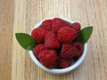 Bowl of red raspberries with peppermeint a juicy are tantalizing their sweet flavor Royalty Free Stock Photos