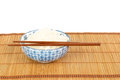 Bowl of rice with chopsticks and table mat against white backgro Royalty Free Stock Photo