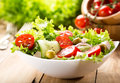 Bowl of salad with vegetables and greens on wooden table Royalty Free Stock Images