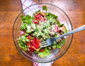 Bowl of salad on wooden table delicious made tomatoes lettuce chicken and olive oil Stock Photo