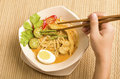 A bowl of savory curry mee noodles in coconut milk gravy Stock Image