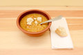 Bowl of soup served with pieces of bread roll torn white on a linen napkin Royalty Free Stock Image