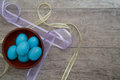 Bowl of speckled blue eggs with pastel ribbon on a rustic table wooden full specked surrounded by sheer ribbons Stock Image
