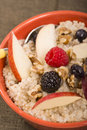 Bowl of steel cut oats served with fresh fruit and honey delicious nuts Stock Photography
