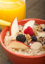 Bowl of steel cut oats served with fresh fruit and honey delicious orange juice Stock Photo