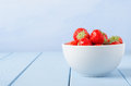 Bowl of strawberries a close eye level side view a white china at right side frame on a light blue painted wood plank table Royalty Free Stock Image