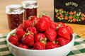 Bowl of strawberries and jars of jam fresh with or jelly Royalty Free Stock Image