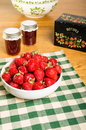 Bowl of strawberries and jars of jam fresh with or jelly Stock Images